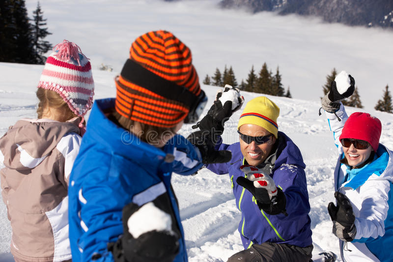 Famille ayant le combat de boule de neige des vacances de ski image stock
