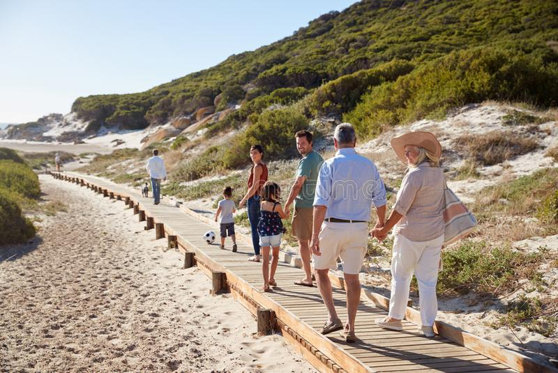 Famille blanche de trois générations marchant ensemble le long d'une promenade en bois sur une plage, intégrale photographie stock libre de droits