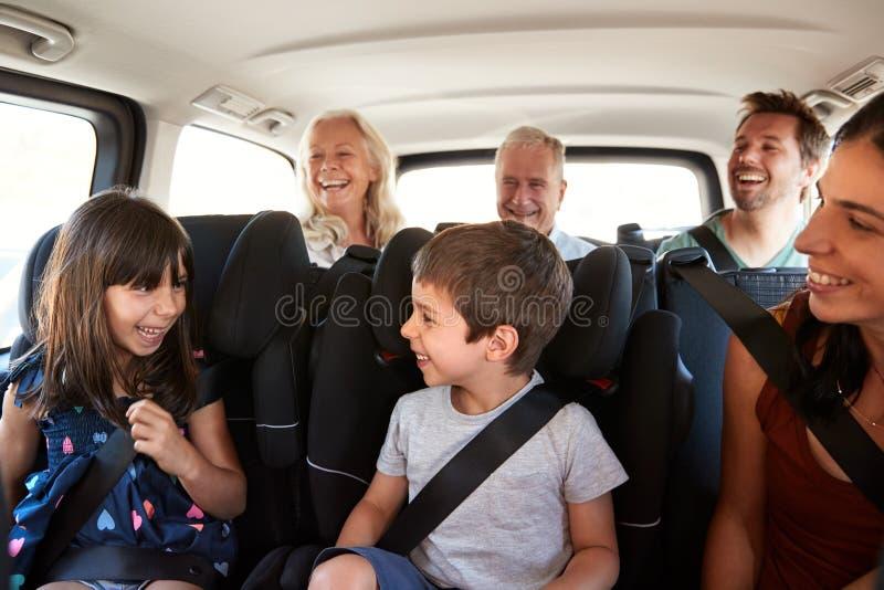 Famille blanche de trois générations se reposant dans deux rangées des sièges de passager dans une voiture, regardant l'un l'autr photographie stock