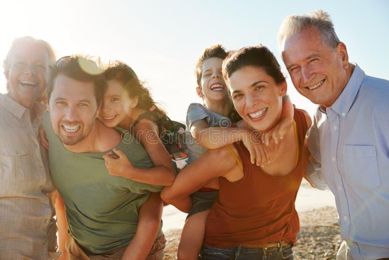 Famille blanche de trois générations sur une plage souriant à la caméra, parents ferroutant des enfants, fin  image libre de droits