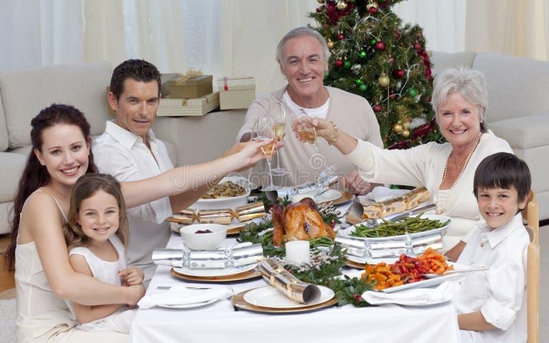 Famille buvant d'un pain grillé dans un dîner de Noël photo stock