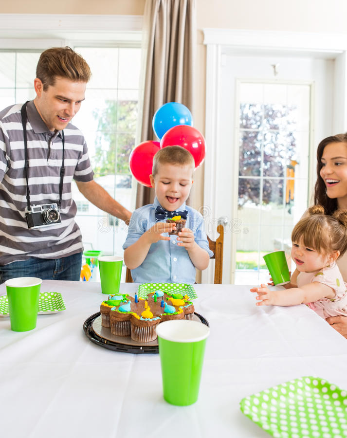 Famille célébrant l'anniversaire du garçon à la maison image stock