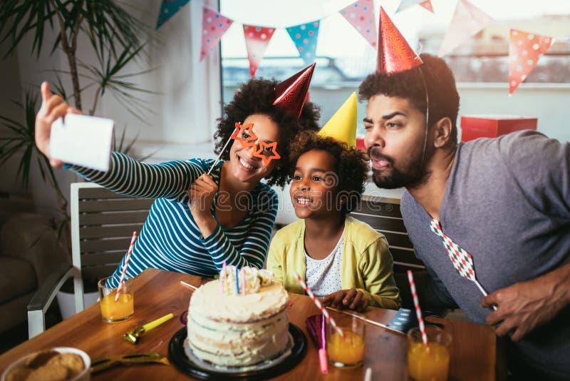 Famille célébrant un anniversaire ensemble à la maison pour faire le selfie image libre de droits