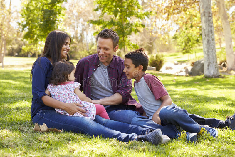 Famille caucasienne asiatique de métis se reposant sur l'herbe en parc photographie stock