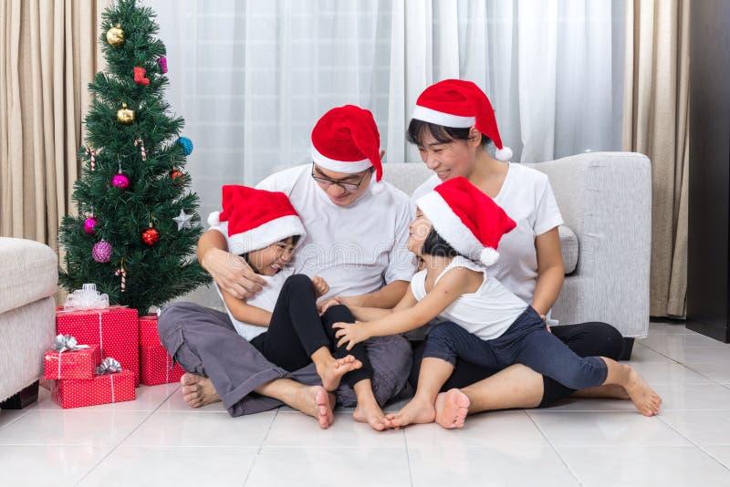 Famille chinoise asiatique heureuse s'asseyant sur le plancher célébrant Chri photo stock