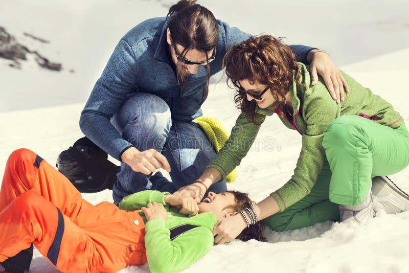 Famille choyant leur fils sur la neige photos libres de droits
