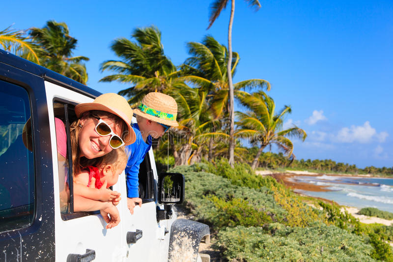 Famille conduisant la voiture tous terrains sur la plage tropicale images stock