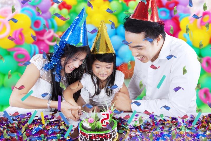 Famille coupant un gâteau d'anniversaire photographie stock