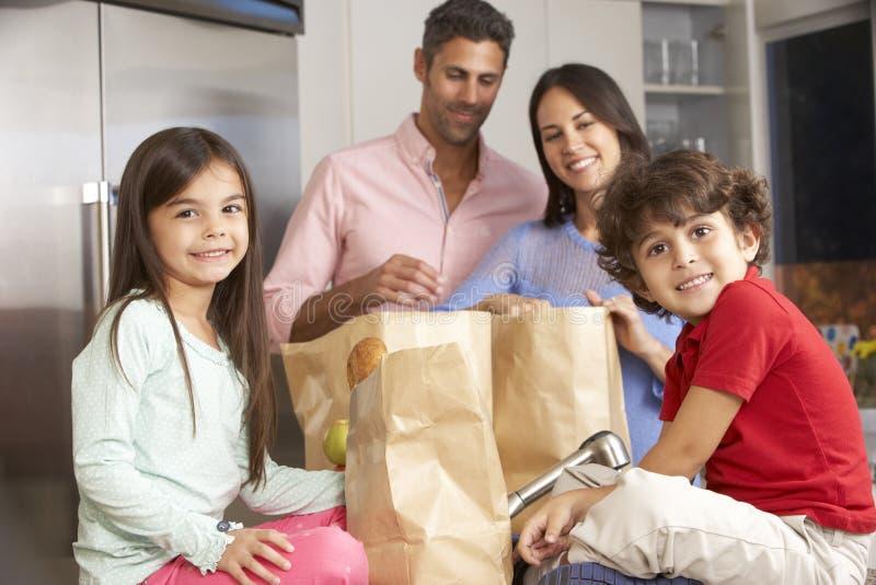 Famille déballant l'épicerie dans la cuisine images stock