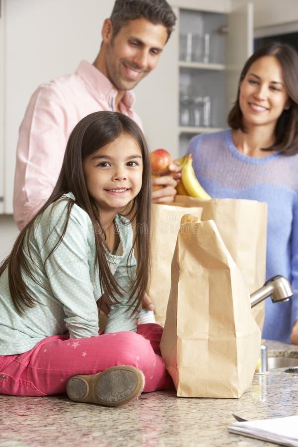 Famille déballant l'épicerie dans la cuisine photographie stock