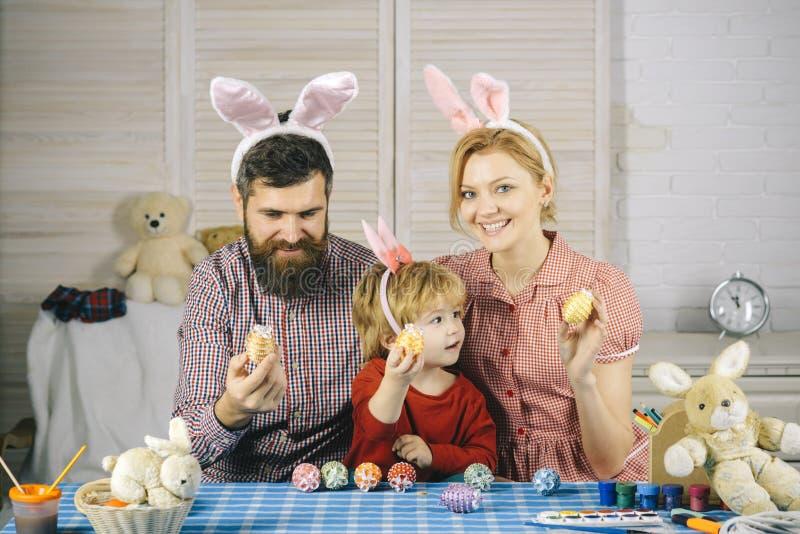 Famille décorant des oeufs de pâques sur le Tableau photographie stock libre de droits