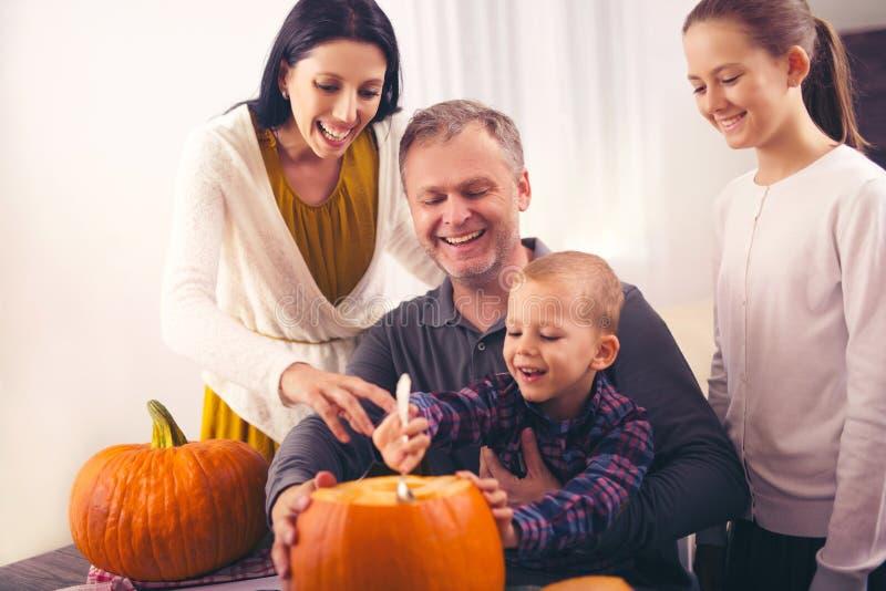 Famille découpant le grand potiron orange pour Halloween images stock