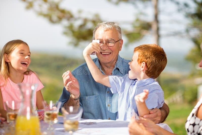 Famille détendant ensemble autour d'une table photographie stock
