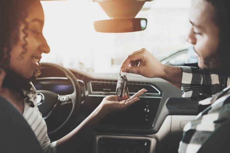 Famille d'afro-américain au concessionnaire automobile La mère et le père sont dans la nouvelle voiture L'homme donne des clés de images libres de droits