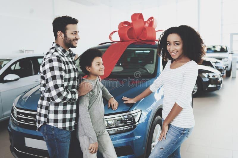 Famille d'afro-américain au concessionnaire automobile Père, mère et fils près de la nouvelle voiture, heureuse photo libre de droits