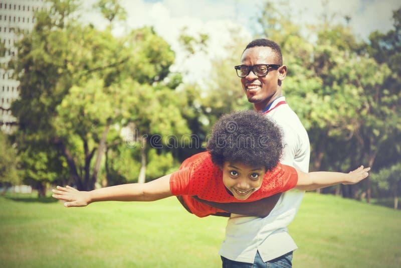 Famille d'afro-américain ayant l'amusement dans le parc extérieur pendant l'été photos stock