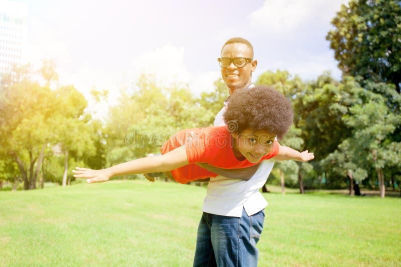 Famille d'afro-américain ayant l'amusement dans le parc extérieur pendant l'été image libre de droits