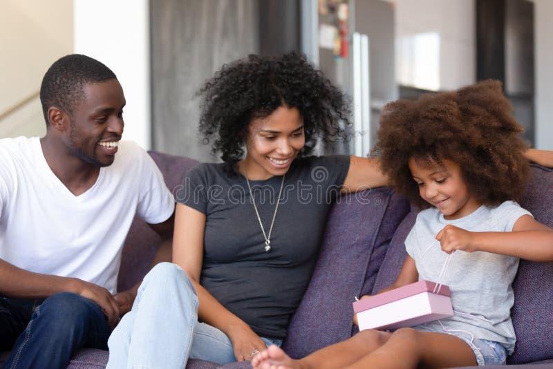 Famille d'afro-américain célébrant l'anniversaire, cadeau d'ouverture de fille photographie stock