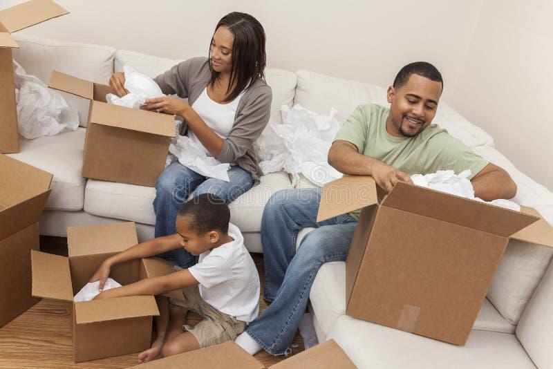 Famille d'afro-américain déballant des boîtes déplaçant la Chambre photo libre de droits