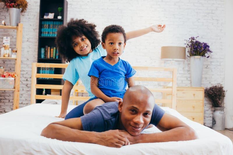 Famille d'afro-américain de trois, enfants s'asseyant sur le dos du ` s de père à la maison images stock