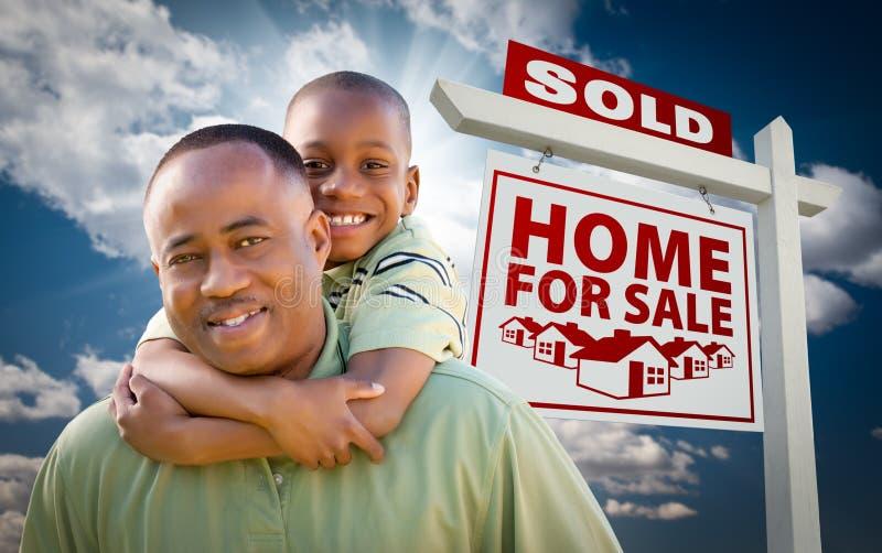 Famille d'Afro-américain devant le signe à la maison vendu photographie stock