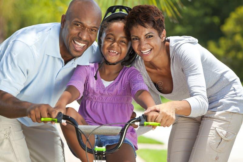 Famille d'Afro-américain et vélo heureux d'équitation de fille photographie stock