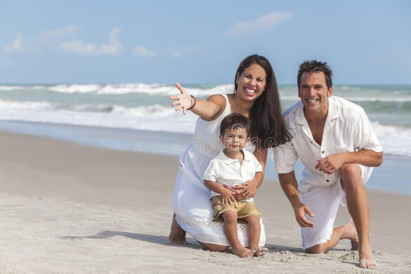 Famille d'enfant de mère, de père et de garçon ayant l'amusement à la plage images libres de droits