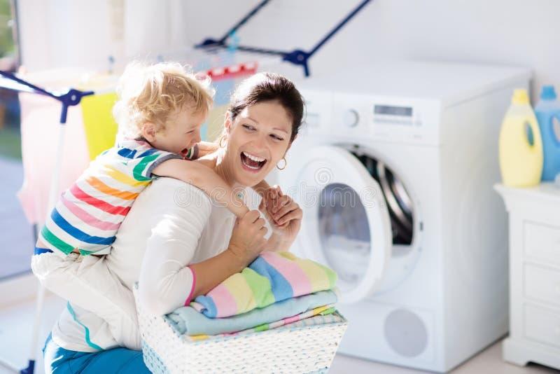 Famille dans la buanderie avec la machine à laver photos stock