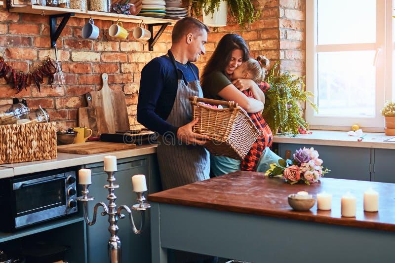 Famille dans la cuisine de style de grenier au matin Le père tient un panier avec des fleurs tandis que mère étreignant avec son  images stock