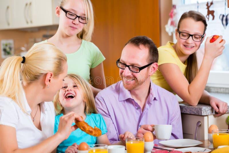 Famille dans la cuisine prenant le petit déjeuner ensemble photos stock