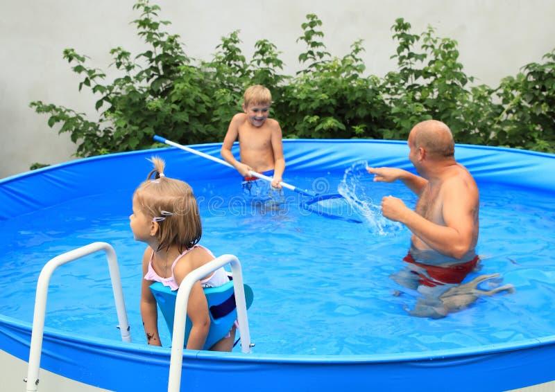 Famille dans la piscine photographie stock libre de droits