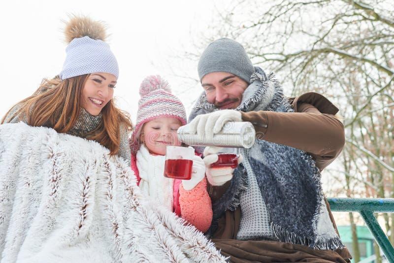 Famille dans la tasse de boissons d'hiver de thé image libre de droits