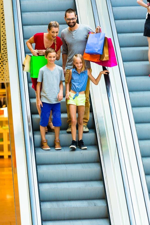 Famille dans le centre commercial sur des escalators avec des sacs photo stock