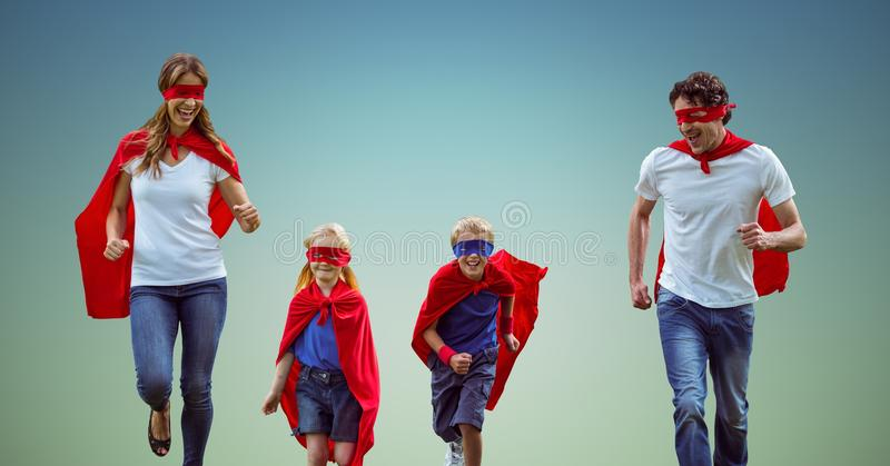 Famille dans le costume de super héros fonctionnant ensemble sur le fond de bleu de ciel image stock