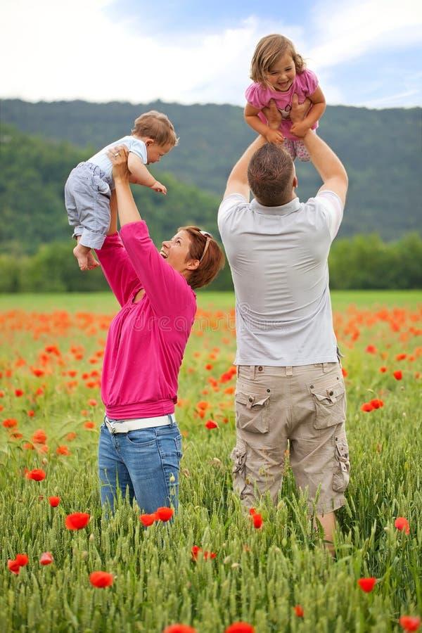 Famille dans le domaine de pavot photographie stock