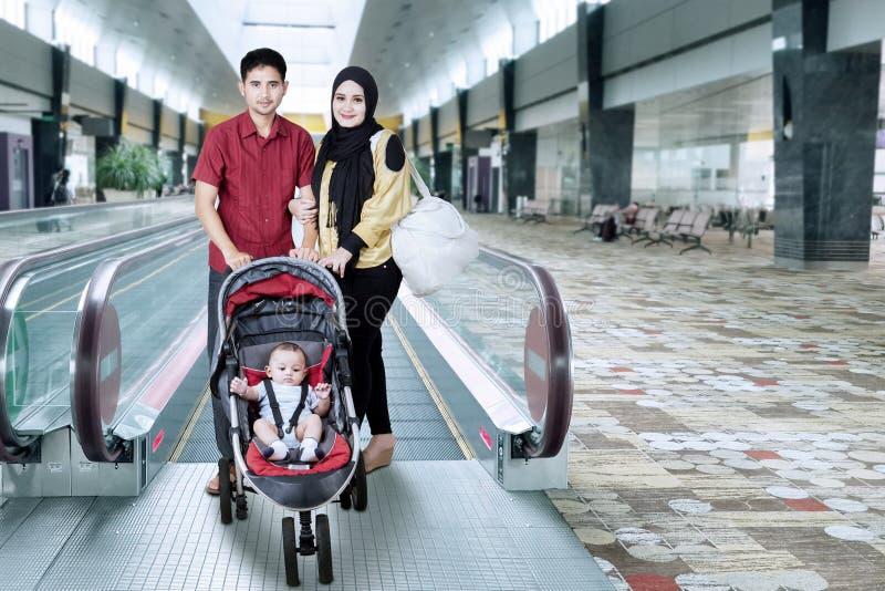 Famille dans le hall d'aéroport avec le bébé sur le landau image libre de droits