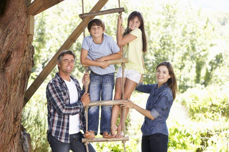 Famille dans le jardin par la cabane dans un arbre images libres de droits