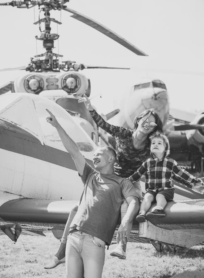 Famille dans le musée d'aviation La mère, le père et l'enfant enthousiaste s'asseyent sur des avions s'envolent dans le musée d'a image libre de droits