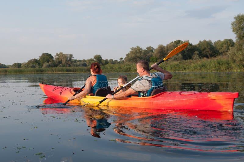 Famille dans un kayak sur une promenade de l'eau photo stock