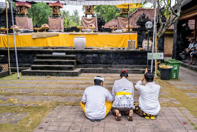 Famille de Balinese habillé dans des costumes traditionnels priant en Pura Goa Lawah Balinese image libre de droits