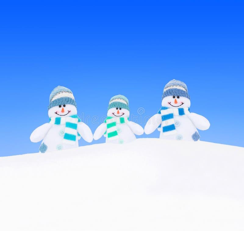 Famille de bonhommes de neige dans des écharpes tricotées à la neige d'hiver contre le ciel images libres de droits
