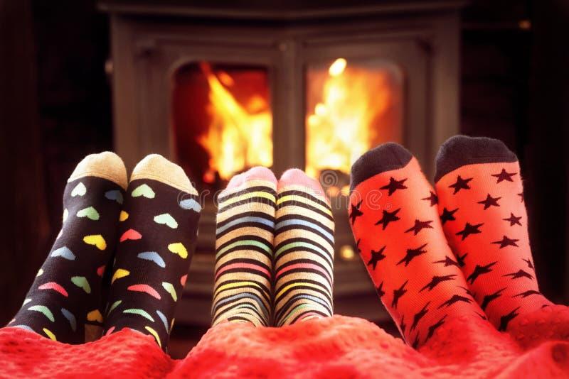 Famille de chaussettes en laine chauffant les pieds par le feu en hiver photographie stock