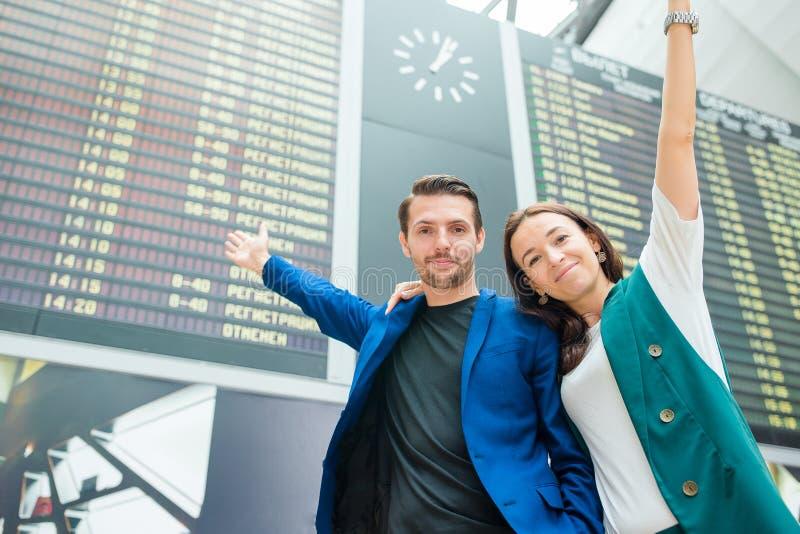 Famille de deux à l'arrière-plan d'aéroport international le conseil de l'information de vol photographie stock libre de droits