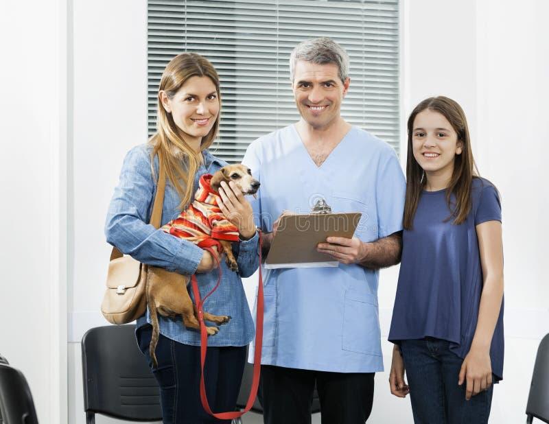 Famille de Holding Clipboard While d'infirmière se tenant avec le teckel images stock