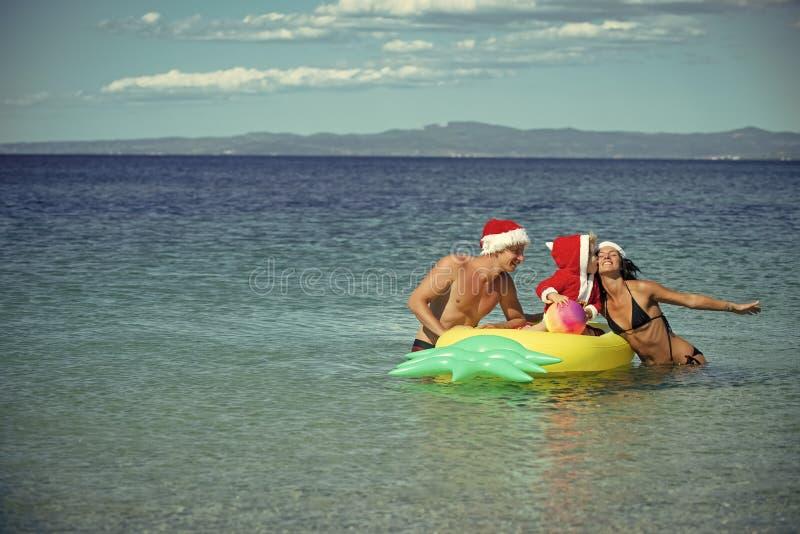 Famille de Noël dans le chapeau de Santa à l'eau de plage avec le matelas photo stock