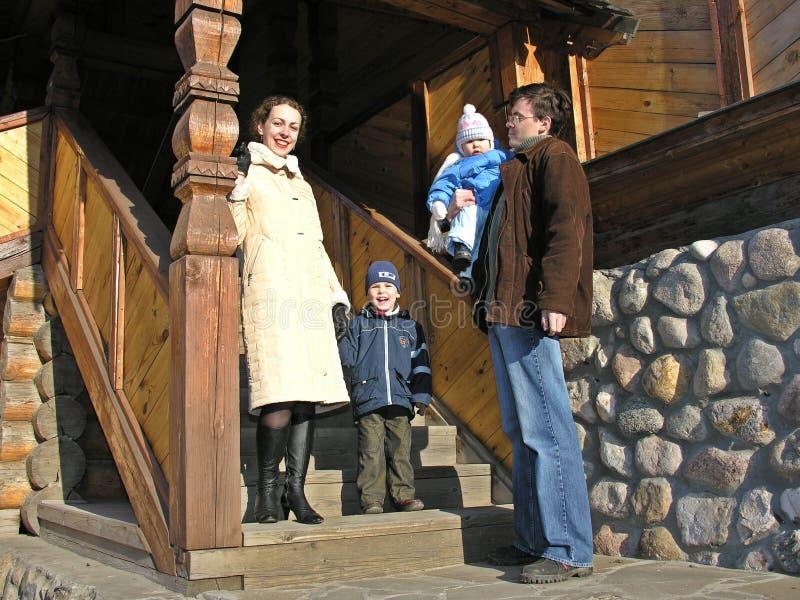 Famille de quatre à l'escalier de la grande maison en bois photos stock