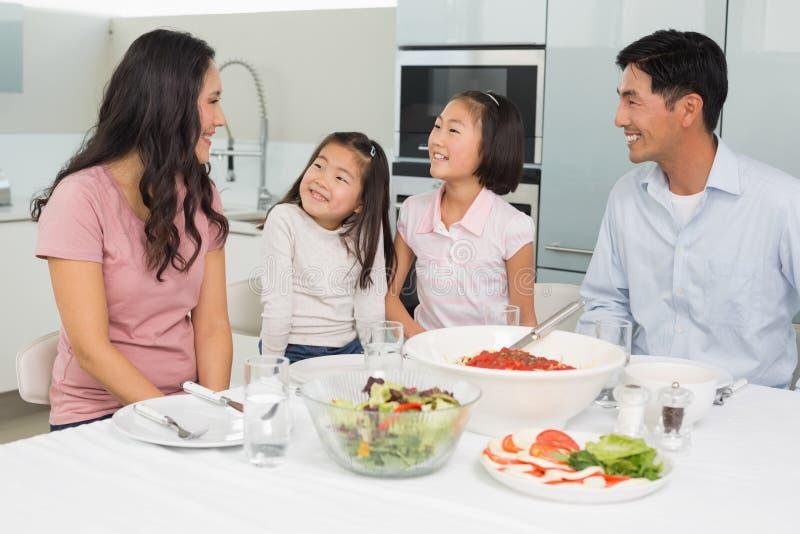 Famille de quatre de sourire se reposant à la table de salle à manger dans la cuisine images libres de droits