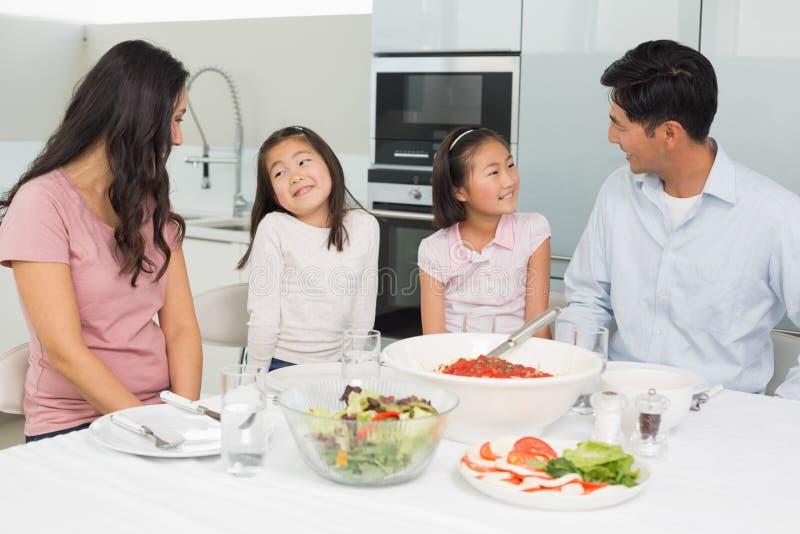 Famille de quatre de sourire se reposant à la table de salle à manger dans la cuisine photos stock
