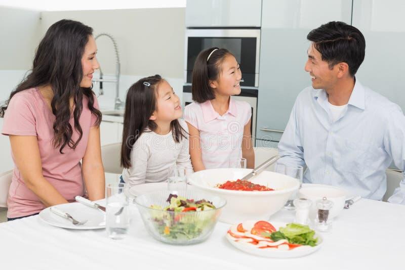 Famille de quatre de sourire se reposant à la table de salle à manger dans la cuisine photo libre de droits