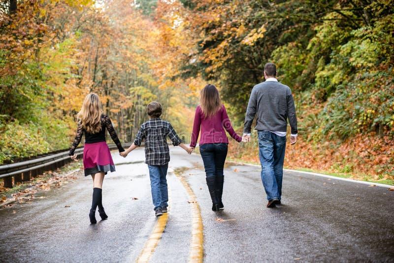 Famille de quatre descendant une route humide tenant des mains photographie stock libre de droits